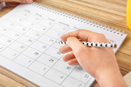 Woman with calendar at wooden table in office, closeup
