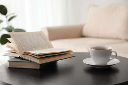 Books and cup of tea on table near modern sofa indoors. Home interior Reklamní fotografie