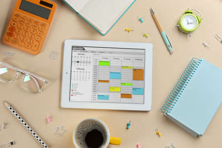 Modern tablet with calendar app on beige background, flat lay Reklamní fotografie