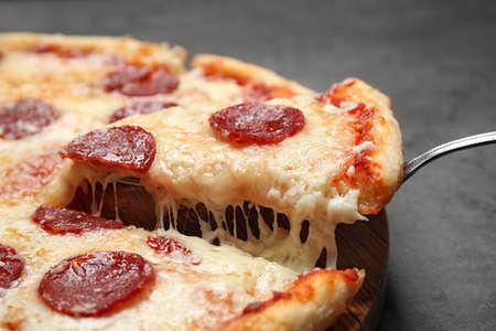 Taking slice of tasty pepperoni pizza on table, closeup Фото со стока