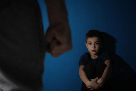 Man threatens his son on blue background. Domestic violence concept Banco de Imagens