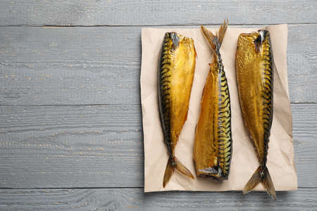 Tasty smoked fish on light grey wooden table, top view. Space for text