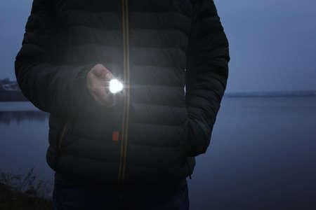 Man with flashlight walking outdoors, closeup view