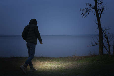 Mann mit Taschenlampe, der abends in der Nähe des Flusses spaziert Standard-Bild