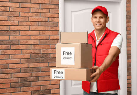 Courier holding parcels with stickers Free Delivery indoors