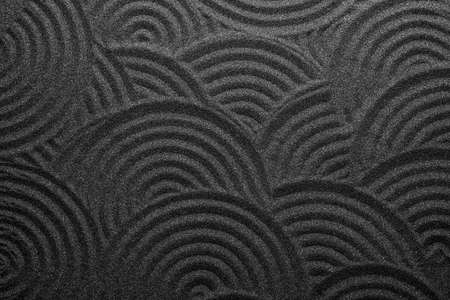 Black sand with beautiful pattern, top view. Zen concept Stock Photo