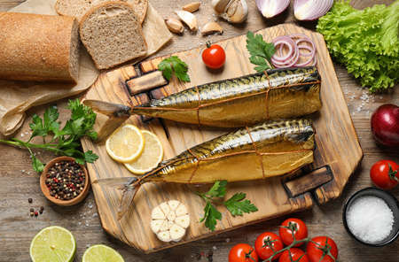 Flat lay composition with tasty smoked fish on wooden table