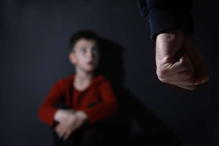 Man threatens his son on black background, focus on fist. Domestic violence concept Banco de Imagens