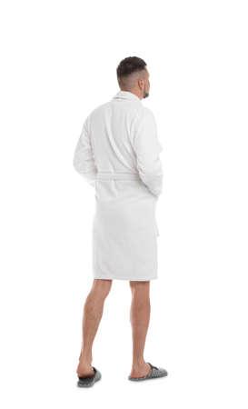 Hombre vestido con albornoz y zapatillas sobre fondo blanco.