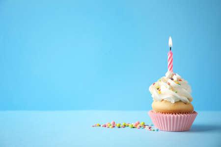 Magdalena deliciosa del cumpleaños con la vela en fondo azul claro. Espacio para texto