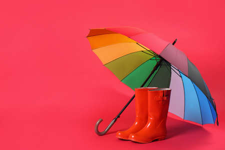 Colorful umbrella and rubber boots on red background. Space for text Stock Photo