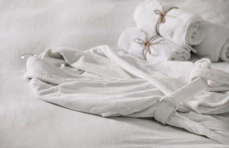 Clean soft bathrobe and towels on bed Foto de archivo