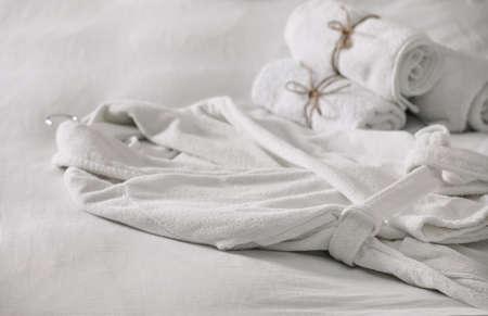 Sauberer weicher Bademantel und Handtücher auf dem Bett Standard-Bild