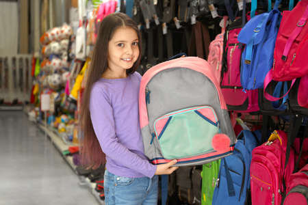 Little school girl with backpack in supermarket Imagens
