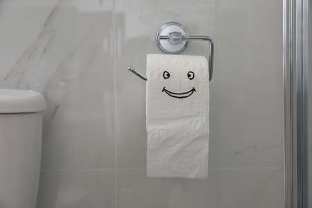 Paper with drawn funny face near toilet tank in bathroom
