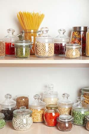 Frascos de vidrio con diferentes tipos de cereales y pasta en estantes de madera