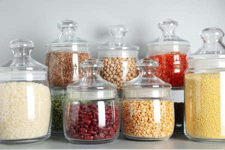 Frascos de vidrio con diferentes tipos de cereales y pastas en estante blanco