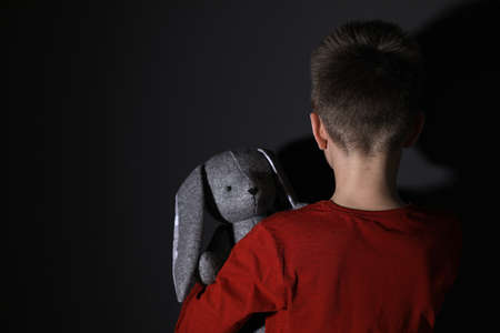 Sad little boy with toy near black wall, back view. Domestic violence concept