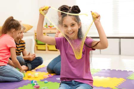 Heureuse petite fille jouant avec du slime dans la chambre