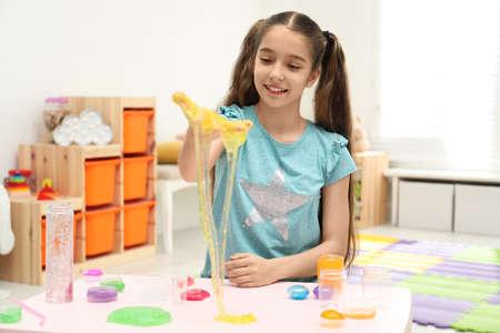 Preteen girl playing with slime à table à l'intérieur Banque d'images