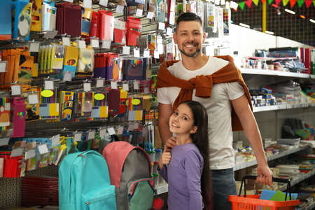 Little girl with father choosing school stationery in supermarket