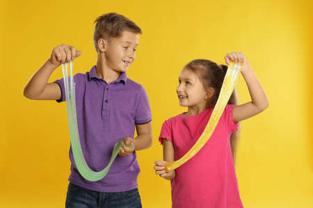 Happy children with slime on yellow background