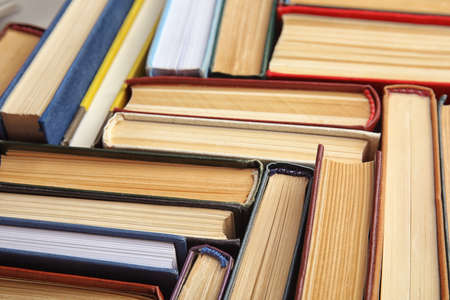 Many different hardcover books as background, closeup