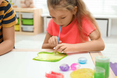 Little girl blowing slime bubble on white table indoors, closeup