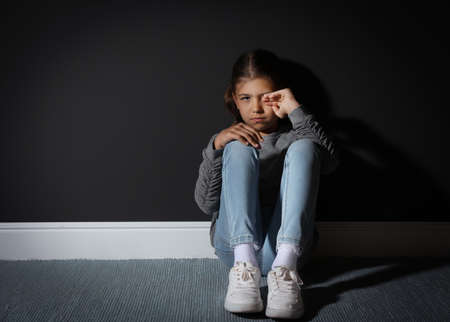 Sad little girl near black wall. Domestic violence concept
