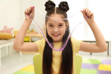 Little girl playing with slime in room