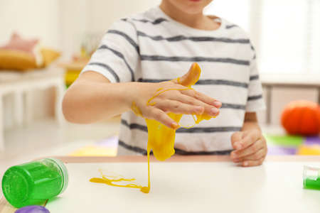 Little boy playing with slime at table indoors, closeup
