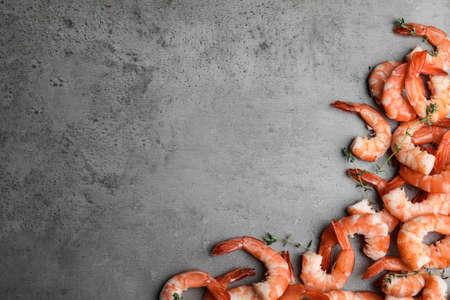 Savoureuses crevettes bouillies au thym sur table grise, à plat. Espace pour le texte Banque d'images