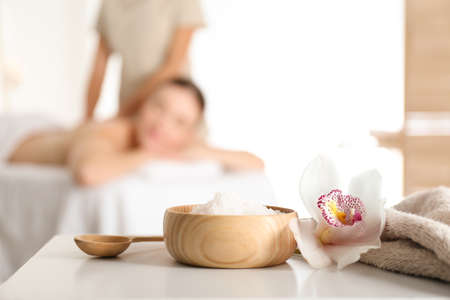 Bowl with sea salt and orchid flower on white table in spa salon. Space for text Reklamní fotografie