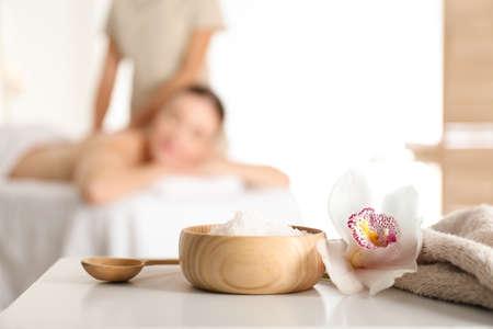 Kom met zeezout en orchideebloem op witte tafel in spa salon. Ruimte voor tekst Stockfoto