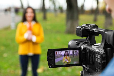 Young journalist and video operator working in park, focus on camera display