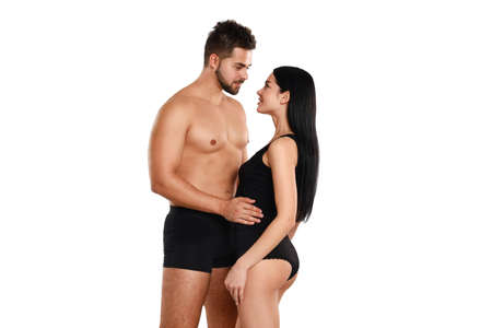 Young couple in black underwear on white background