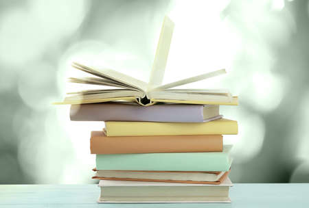 Stack of different books on table against blurred background
