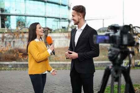Joven periodista entrevistando al empresario en las calles de la ciudad Foto de archivo