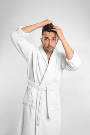 Young man in bathrobe on white background