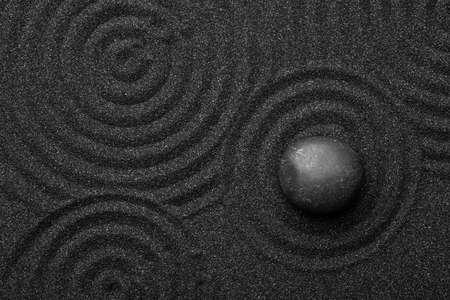 Schwarzer Sand mit Stein und schönem Muster, Draufsicht. Zen-Konzept
