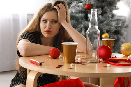 Young woman suffering from hangover at messy table after New Year party