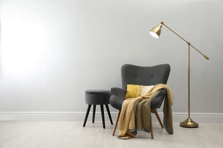 Stylish armchair with plaid, floor lamp and ottoman near white wall, space for text. Interior design