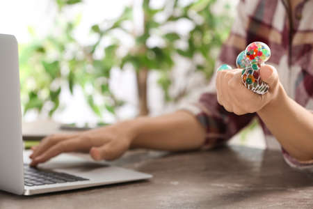 Woman squeezing colorful slime in office, closeup. Antistress toy