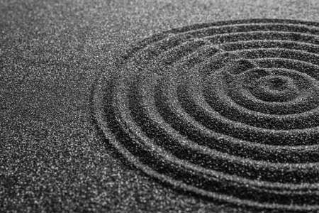 Black sand with beautiful pattern, closeup. Zen concept Stock Photo