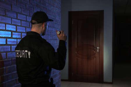 Männlicher Wachmann mit Taschenlampe im dunklen Korridor