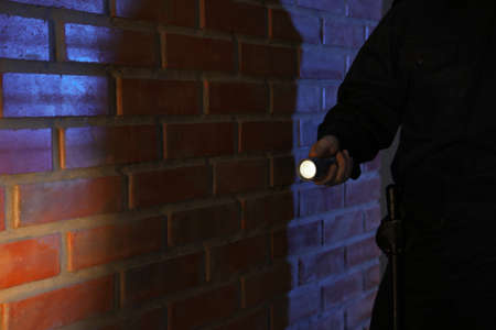 Male security guard with flashlight near brick wall in darkness