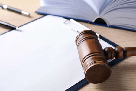Clipboard with words DOMESTIC VIOLENCE and gavel on wooden table, closeup Reklamní fotografie