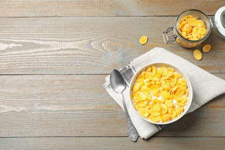 Flache Zusammensetzung mit leckeren Cornflakes auf Holztisch, Platz für Text Standard-Bild