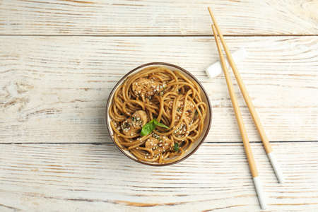 Tasty buckwheat noodles with meat on white wooden table, flat lay