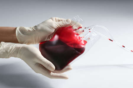 Woman holding blood for transfusion on light background, closeup. Donation concept Archivio Fotografico